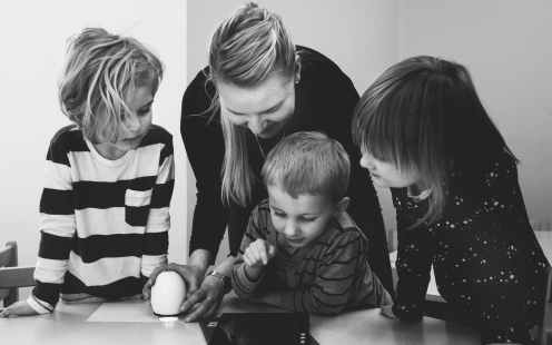 grayscale photo of mother and three children playing
